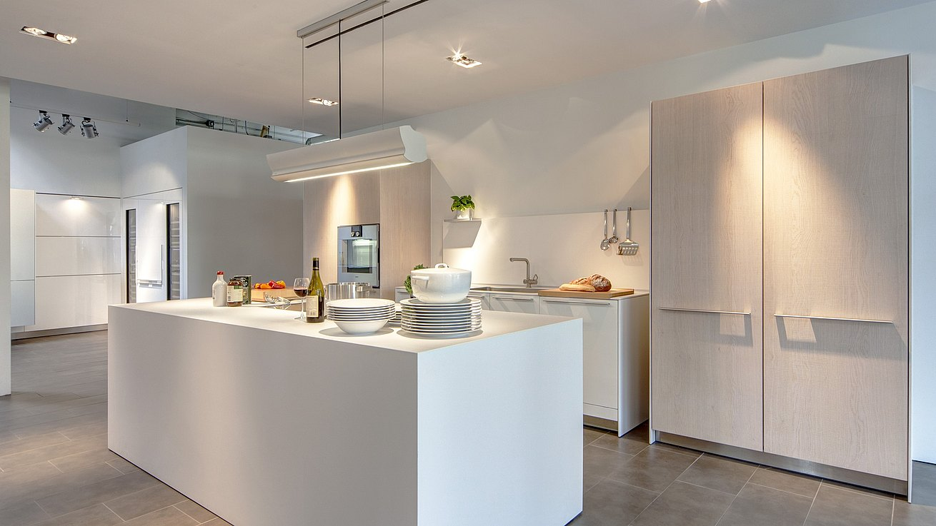 b3 kitchen in white laminate and oak with dishes and meal preparation ingredients set out on the island.