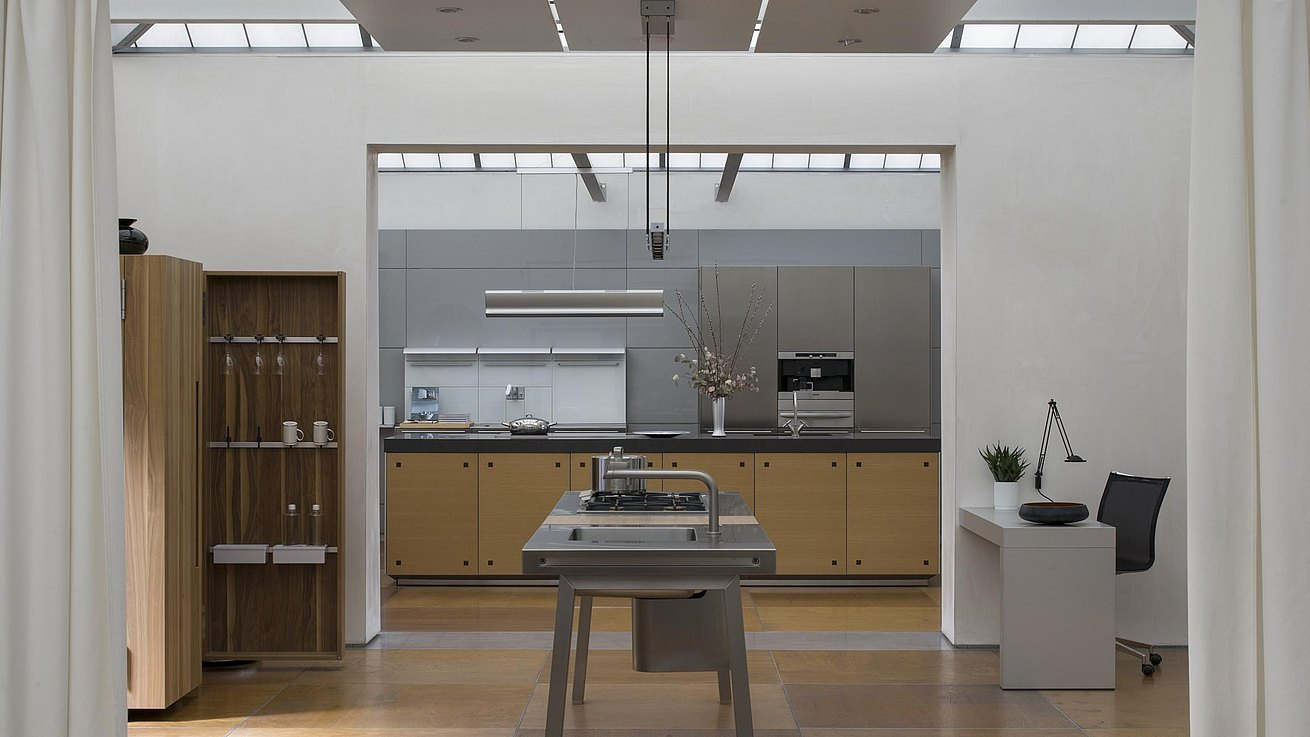 Interior of showroom with b2 workbench in stainless steel and b2 cabinet in walnut in the forefront and a b3 kitchen in the background.