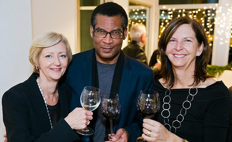 Three guests posing for the photo cheering with their glasses of wine.