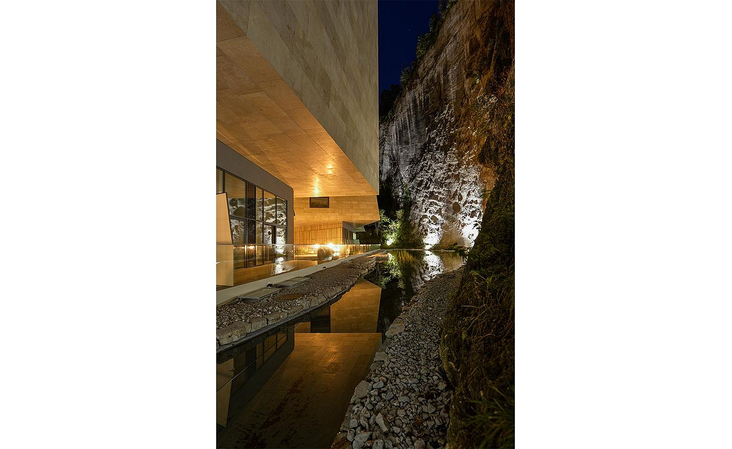 Exterior view at night: modern structures are reflected in the pond in front of the rock face