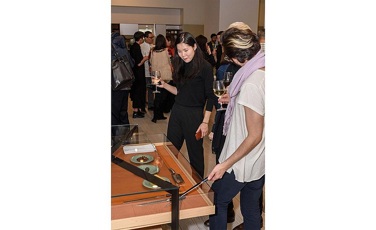 Guests viewing and interacting with special chef items and ingredients in b Solitaire Glass pull out tray with leather inlay.