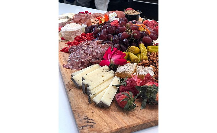 Beautiful display of wooden cutting board filled with a variety of delicious cheese, meat, and fruit