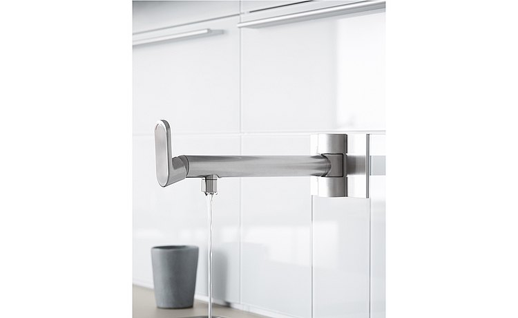 Wall-mounted, swiveling faucet at the water point