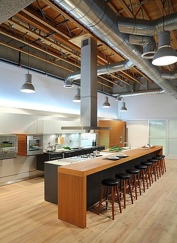 Long view of showroom showing b3 kitchen in grey anodized aluminum and horizontal walnut and featuring a view of the exposed ceiling.