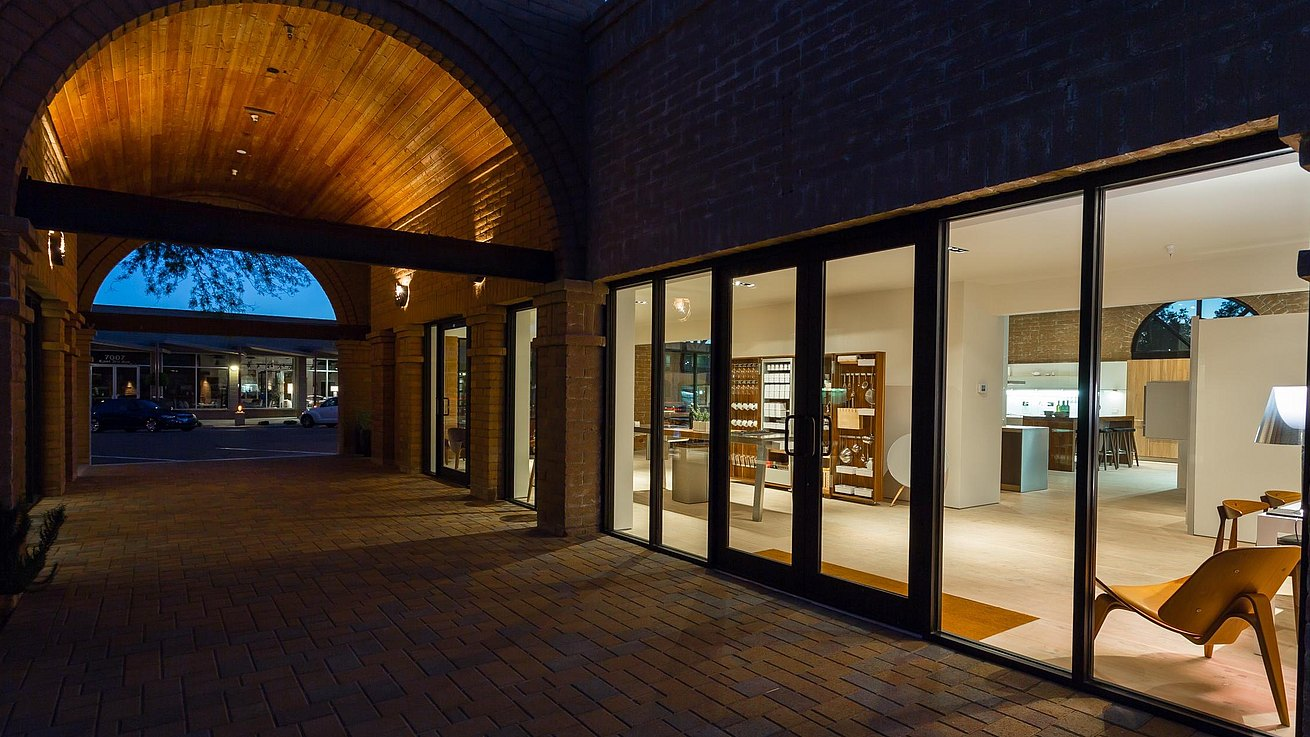 Night view into showroom from building's arched corridor.