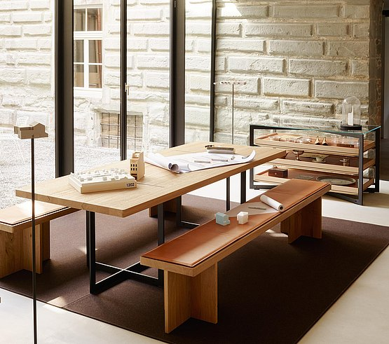 The table's aluminum frame harmonizes with the bench's oak base by expressing the same design principle of intersecting planes/lines that form an X or cross.