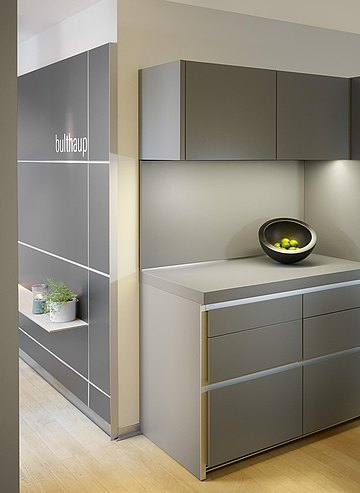 Details of b1 kitchen in gravel laminate and functional wall with shelf and hanging pot.