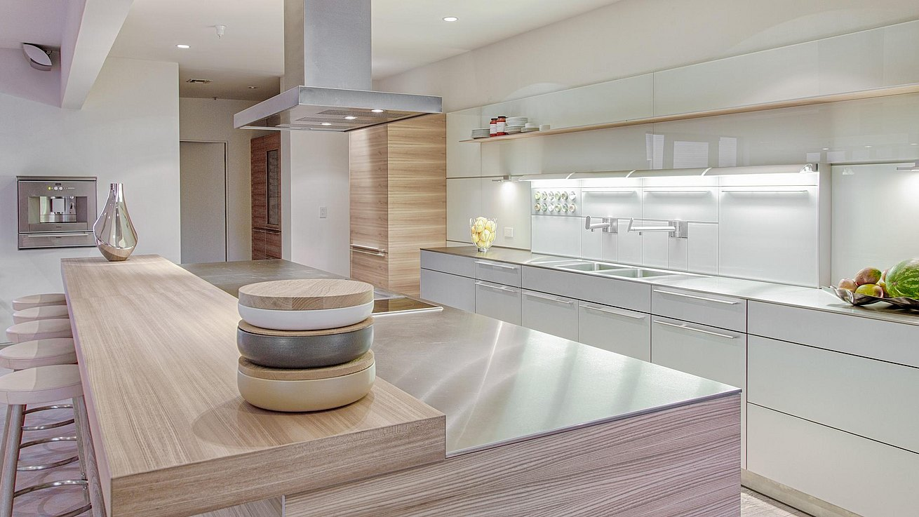 b3 kitchen in natural aluminum with island in Elm wood veneer, stainless steel countertop and bar top in Elm veneer.