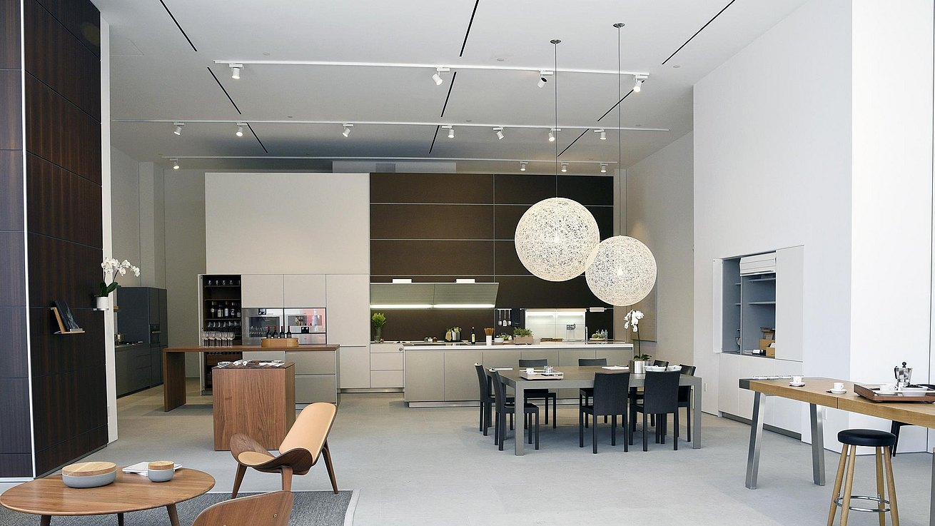 Showroom view showing b3 kitchen in anodized aluminum, white laminate and stainless steel, c2 table in gray and b2 workbench.