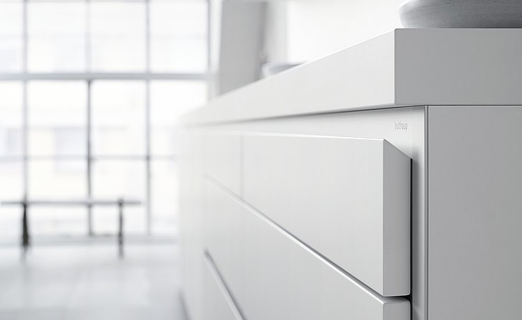 The front panel of the door and drawer elements, which angles down, forms an ergonomic and  unique handle system