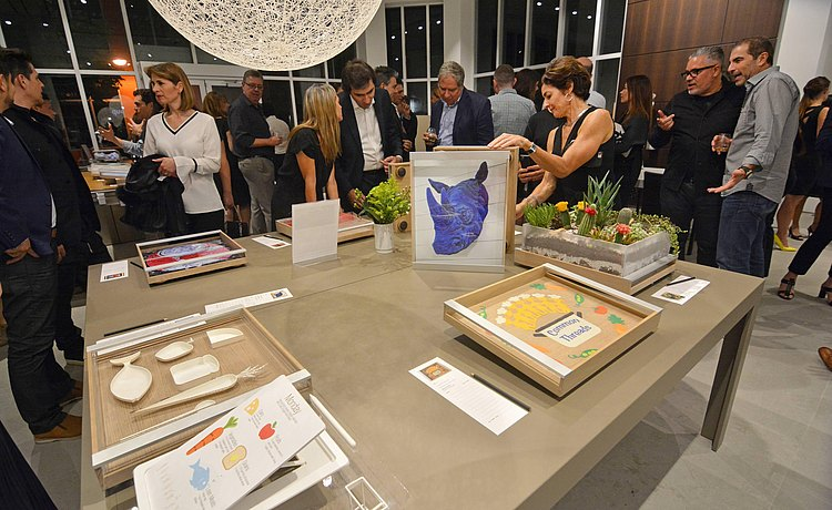 Overall view of guests mingling around the displayed art piece trays.