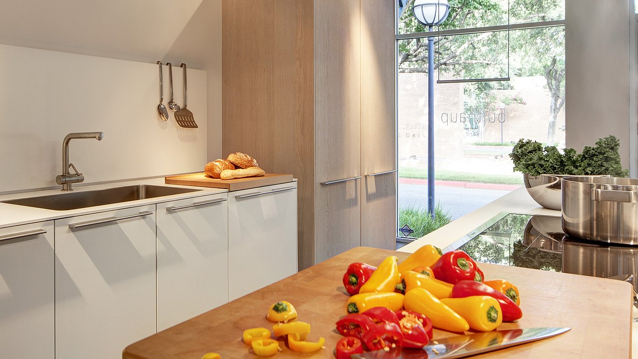 Detail of b3 kitchen in white laminate and oak featuring bulthaup chopping block with red and yellow peppers in the midst of being chopped.