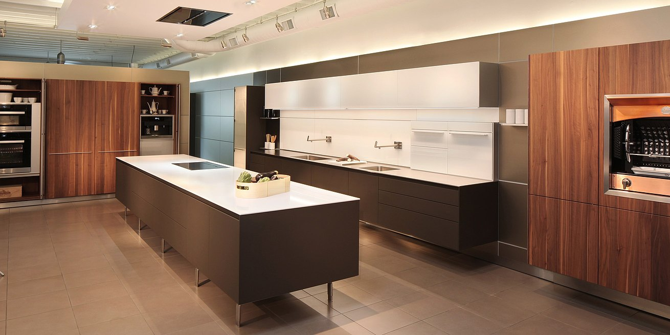 b3 kitchen in soft touch lacquer Cashmere, Solid walnut, glass wall cabinets and panels, featuring foot mounted island and hanging kitchen with tall pocket door cabinets open.