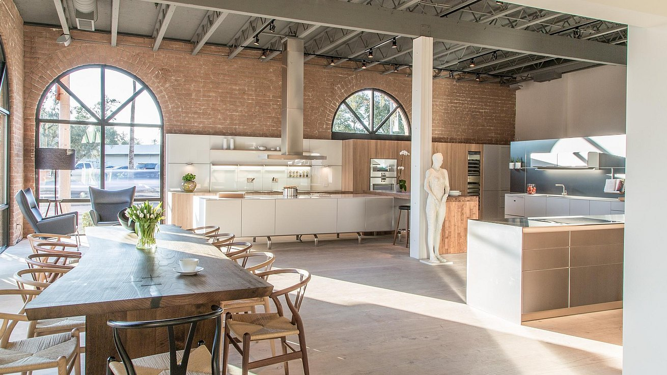 Wide view of showroom featuring exposed brick walls and ceiling, b3 kitchen displays and a dining table with Carl Hansen chairs.