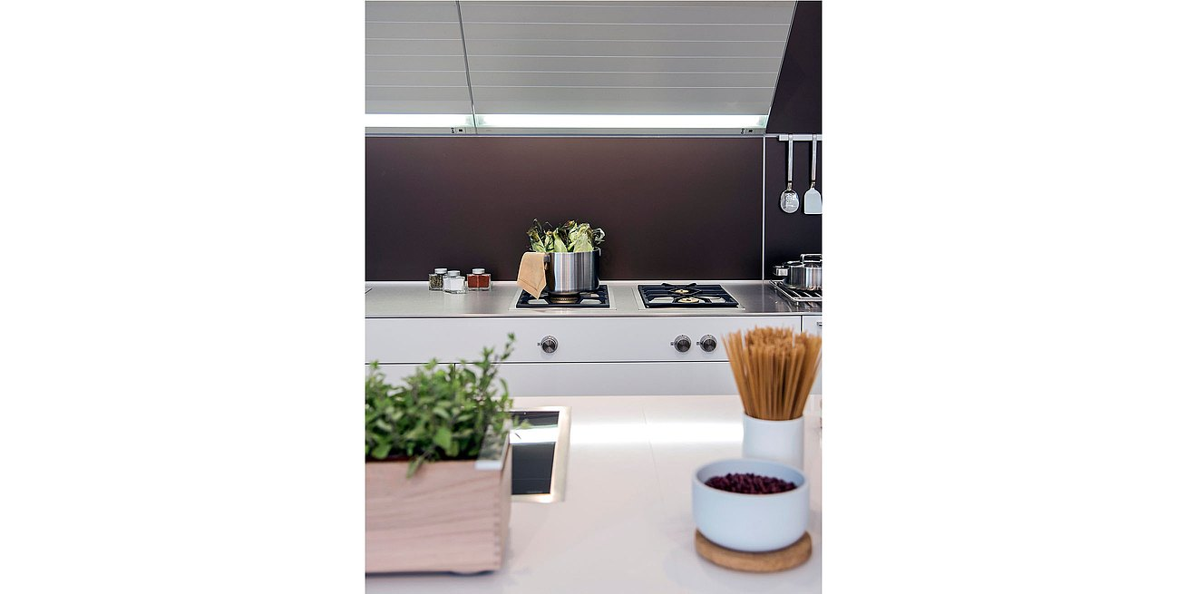 Detail of b3 kitchen featuring bulthaup extractor with aluminum slats and light element.