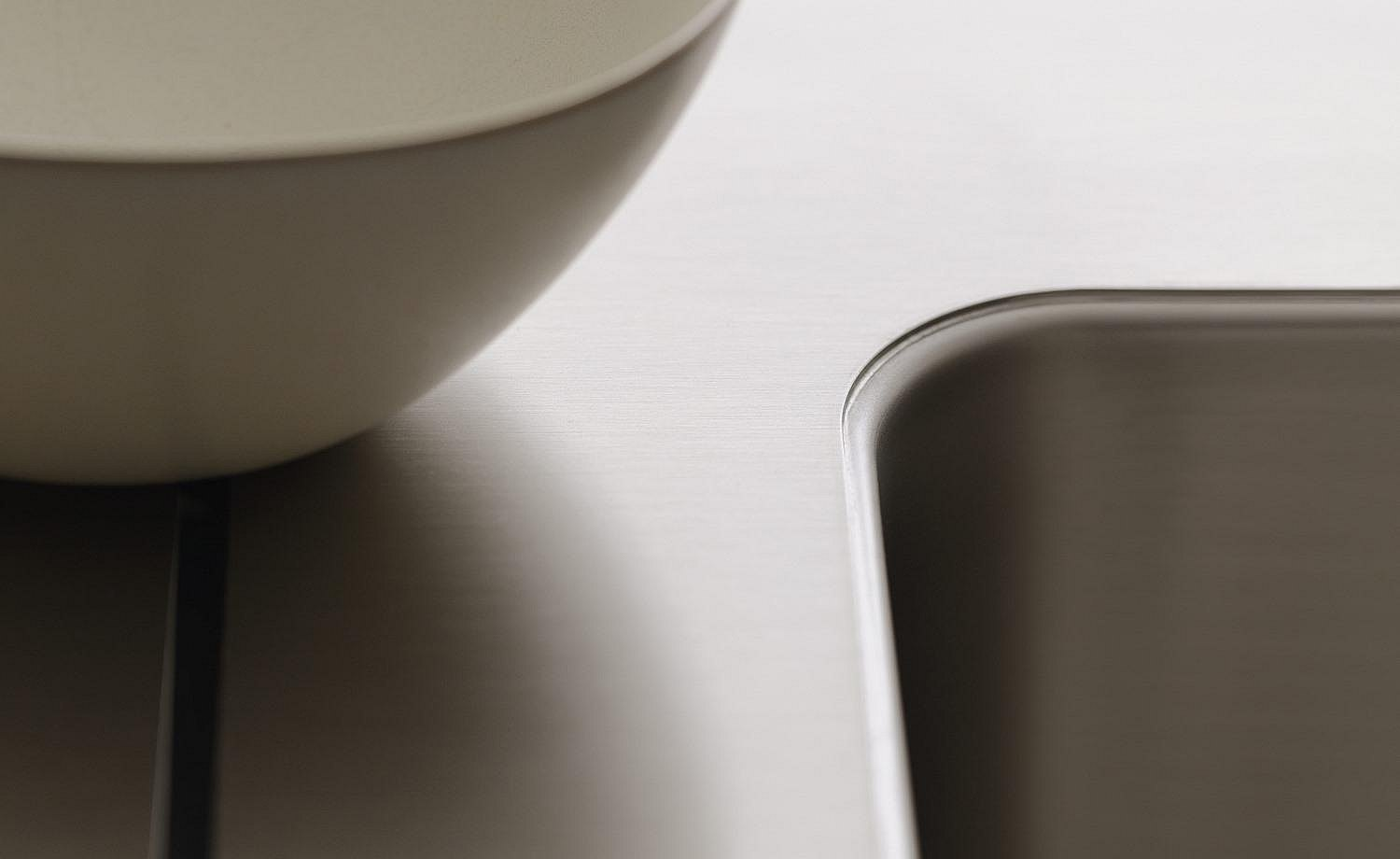 Close-up: brushed stainless steel water point, integrated seamlessly into the workbench