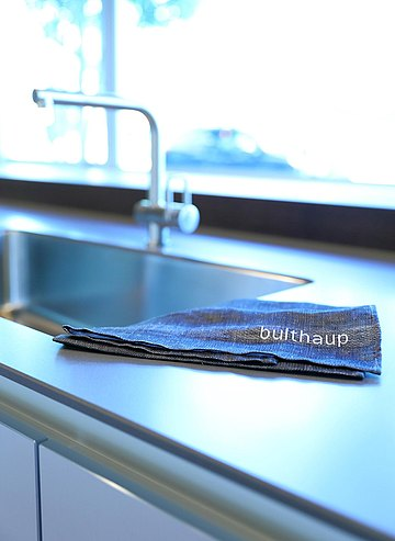 Detail of grey synthetic stone counter top with bulthaup linen towel.