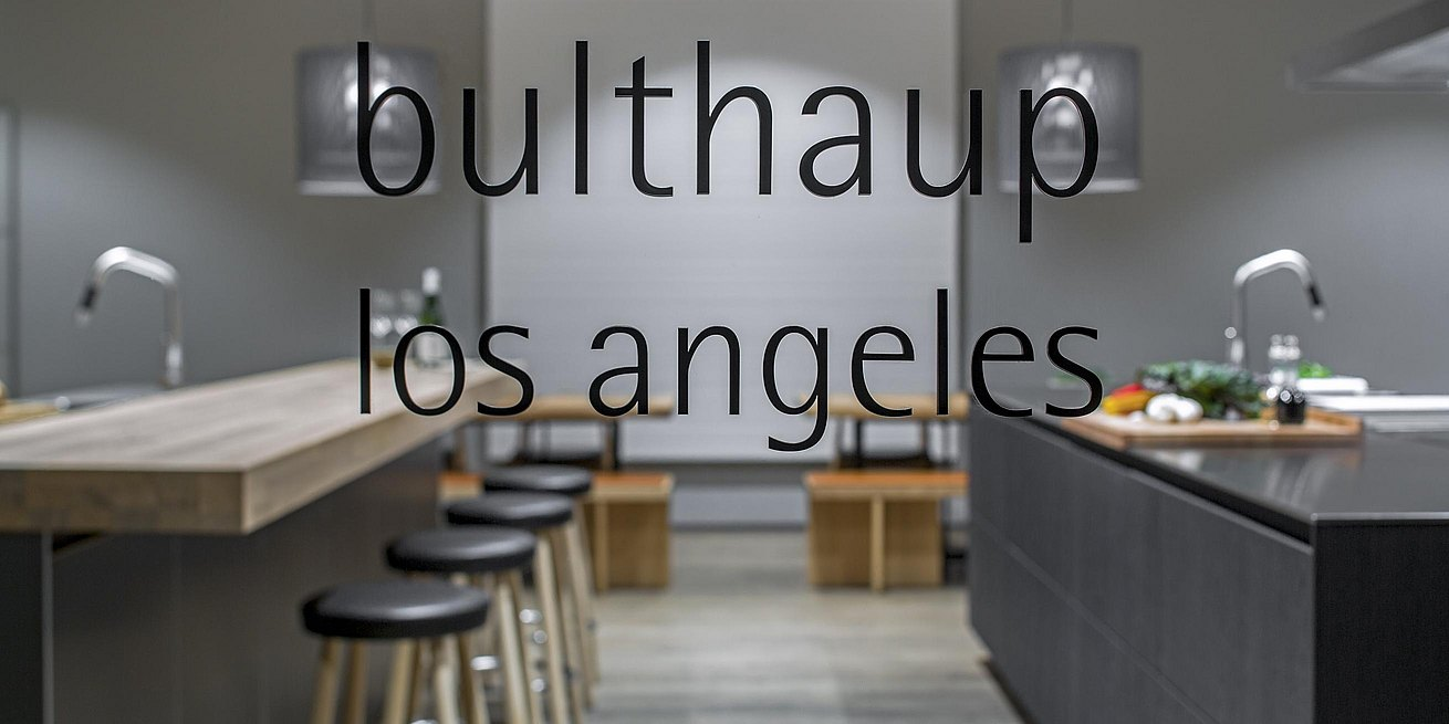 View through showroom window of kitchen island displays with bulthaup los angeles logo appearing.