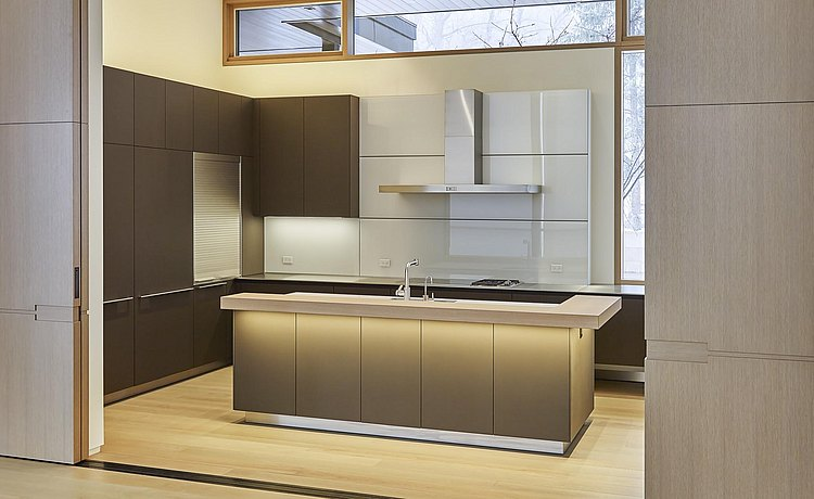 A view looking into the kitchen framed by large custom wood sliding doors. Inside material selected included sand beige aluminum for the island and soft touch lacquer tall elevation and base cabinets floating on wall with a backsplash made of white glass.