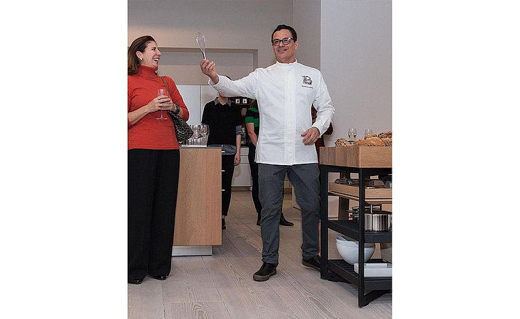 Chef Dani happily gesturing to the guests in his presentation standing next to our b Solitaire Oak.