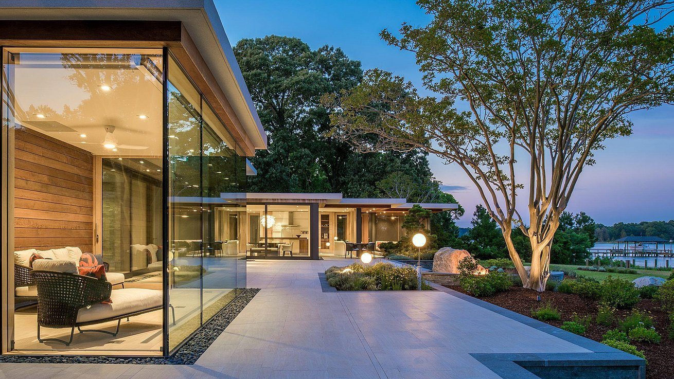 Exterior front of house at dusk with floor to ceiling windows and deck facing out to a large front yard and waterfront.