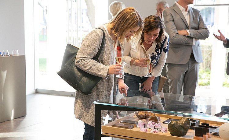 Two guests peering into the glass top of bulthaup b Solitaire and pointing to items that have drawn their attention.