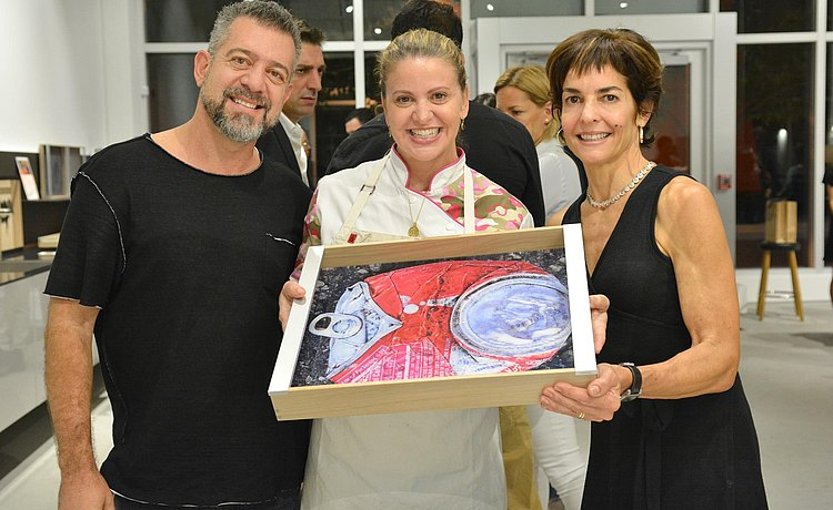 Chef Michelle Bernstein holding one of the art piece trays with guests.