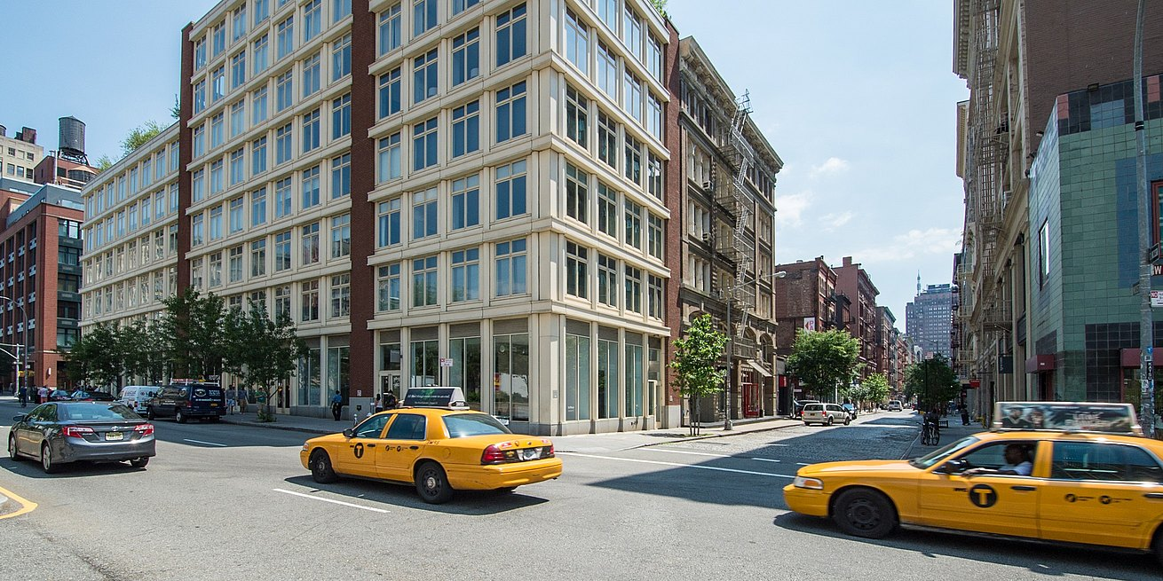 Exterior street view of New York showroom with yellow taxi cabs passing by.