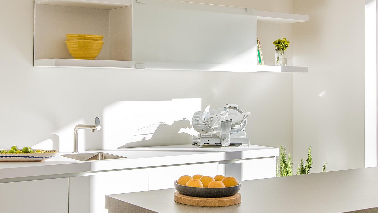 b1 kitchen in alpine white laminate featuring shelf unit with sliding translucent glass panel.
