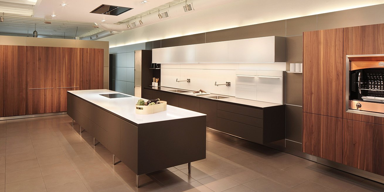 b3 kitchen in soft touch lacquer Cashmere, Solid walnut, glass wall cabinets and panels, featuring foot mounted island and hanging kitchen with tall pocket door cabinets closed.