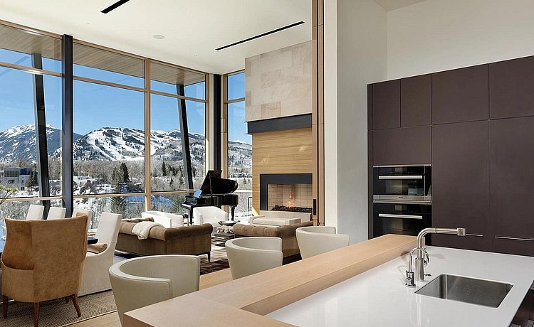 Partial view of living space and kitchen space including bar top finished in natural oak. Tall elevation where appliances are located finished in soft touch lacquer. Countertop is white quartz. A beautiful backdrop of the Aspen mountain range.