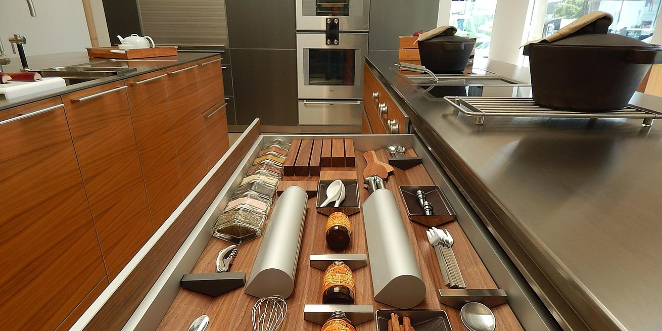 Detail of prism drawer with bulthaup spice jars and foil holders in b3 kitchen in walnut and stainless steel.
