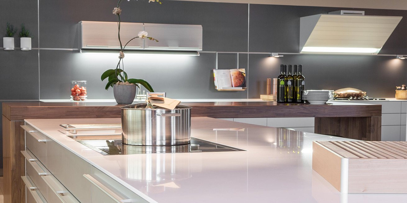 b3 island with walnut bar top in front of grey anodized aluminum functional wall system featuring bulthaup extractor hood with aluminum slats.