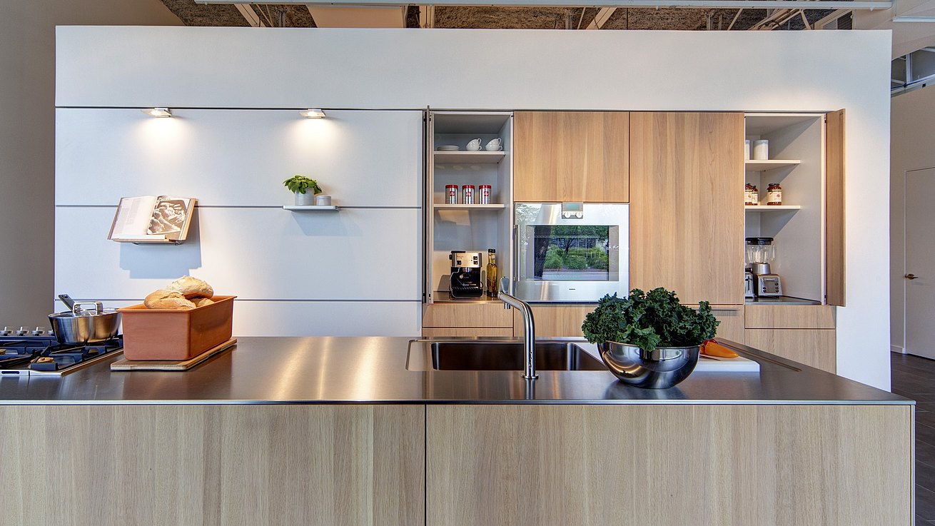 b3 kitchen in oak and stainless steel with wall panel system in alpine white featuring cookbook holder, small shelf and lights installed in the bulthaup function gap.
