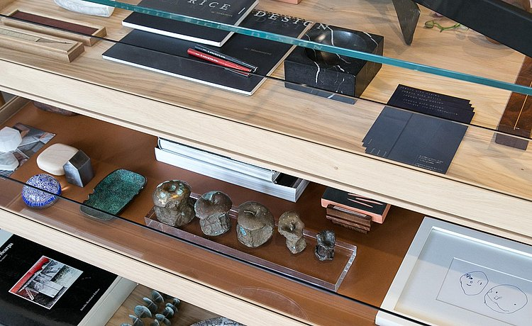 Detail of designer Joshua Rice's collection viewed through the glass top of our b Solitaire showing notebooks, favored pens and other special objects.
