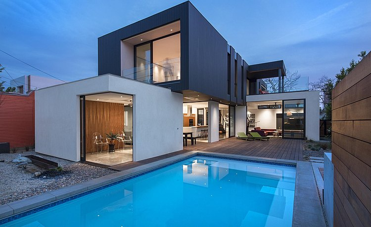 Exterior view at dusk of contemporary style house with swimming pool and deck and view of b3 kitchen inside the very open plan architecture.