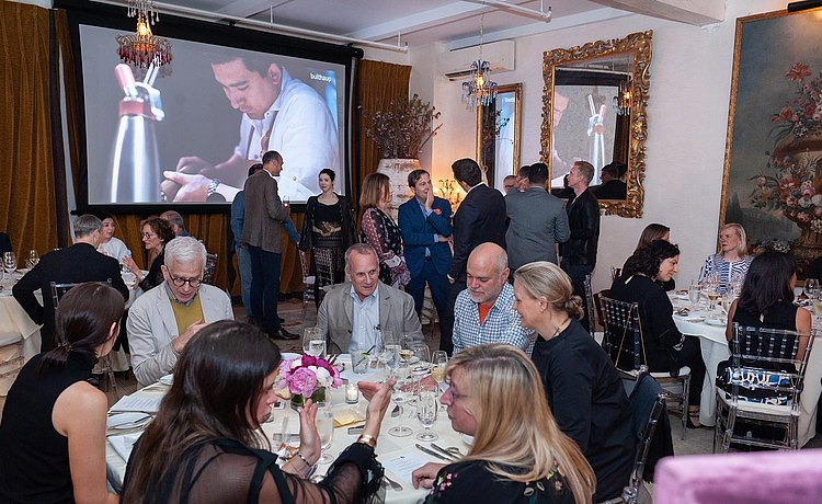 Guests seated and standing at the start of a special dinner party at Bouley Test Kitchen with video of bulthaup Milan 2018 presentation on screen.