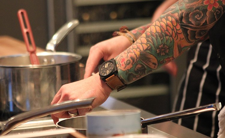 Chef arm with sleeve tattoo preparing a dish at b3 island.