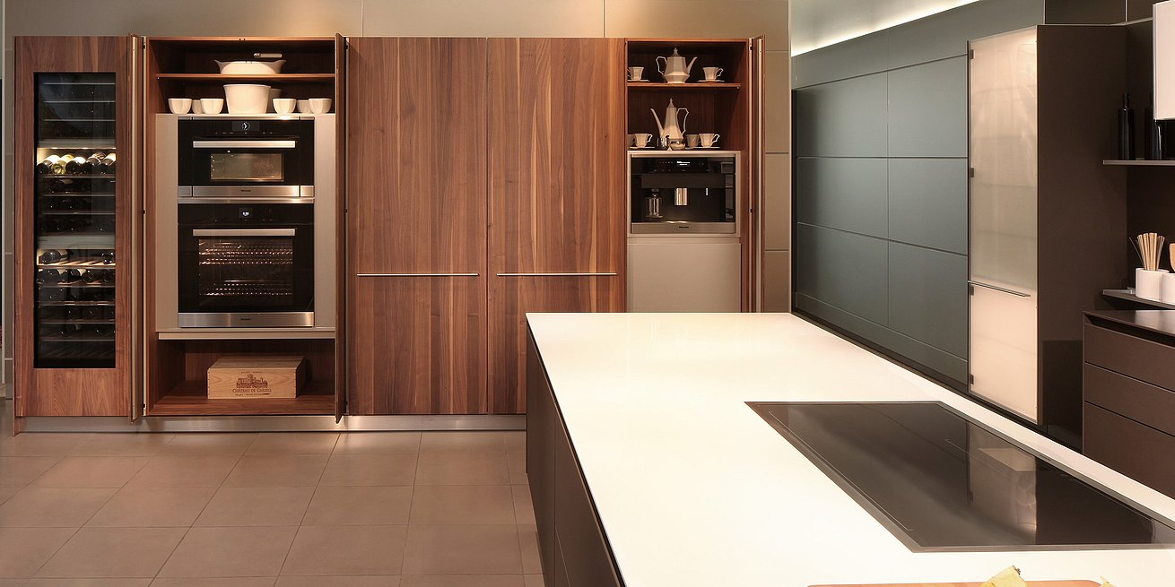 Detail view of b3 cabinets in Solid walnut with doors open showing housed appliances and stored accessories.