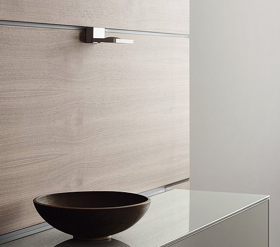 Elegant lighting element above the work surface, attached to the functional rear wall