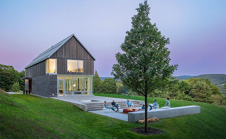 Exterior view of house in rural Vermont with people gathered around the fire pit.