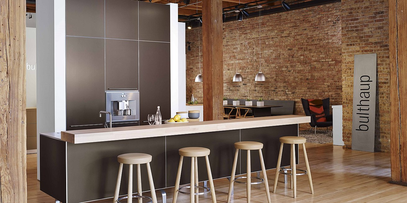 b3 kitchen in bronze anodized aluminum and wide view of showroom featurin exposed brick walls and - Kitchen Chicago