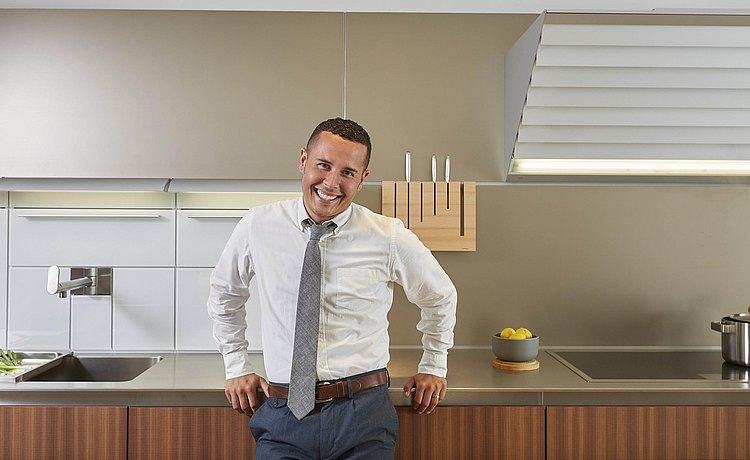 bulthaup designer Alexander Morrison leaning casually against b3 stainless steel countertop.