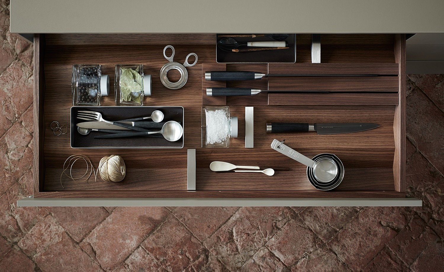 Well organized drawer with dark wood prisms and equipment elements: stainless steel containers, knife block, and stainless steel dividers