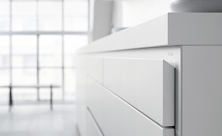The edge of the drawer front angles down to create a natural and ergonomic handle. Link: Learn more about the handle system