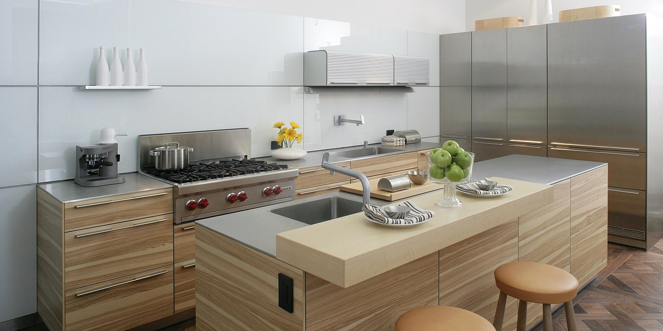b3 kitchen in apple wood and stainless steel with bar top in oak and panel wall system in white glass.