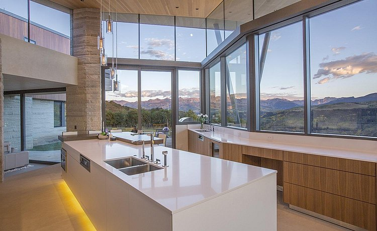 b3 kitchen in walnut and alpine white lacquer featuring an angled installation to follow the line of the architecture that showcases beautiful mountain views from expansive windows.