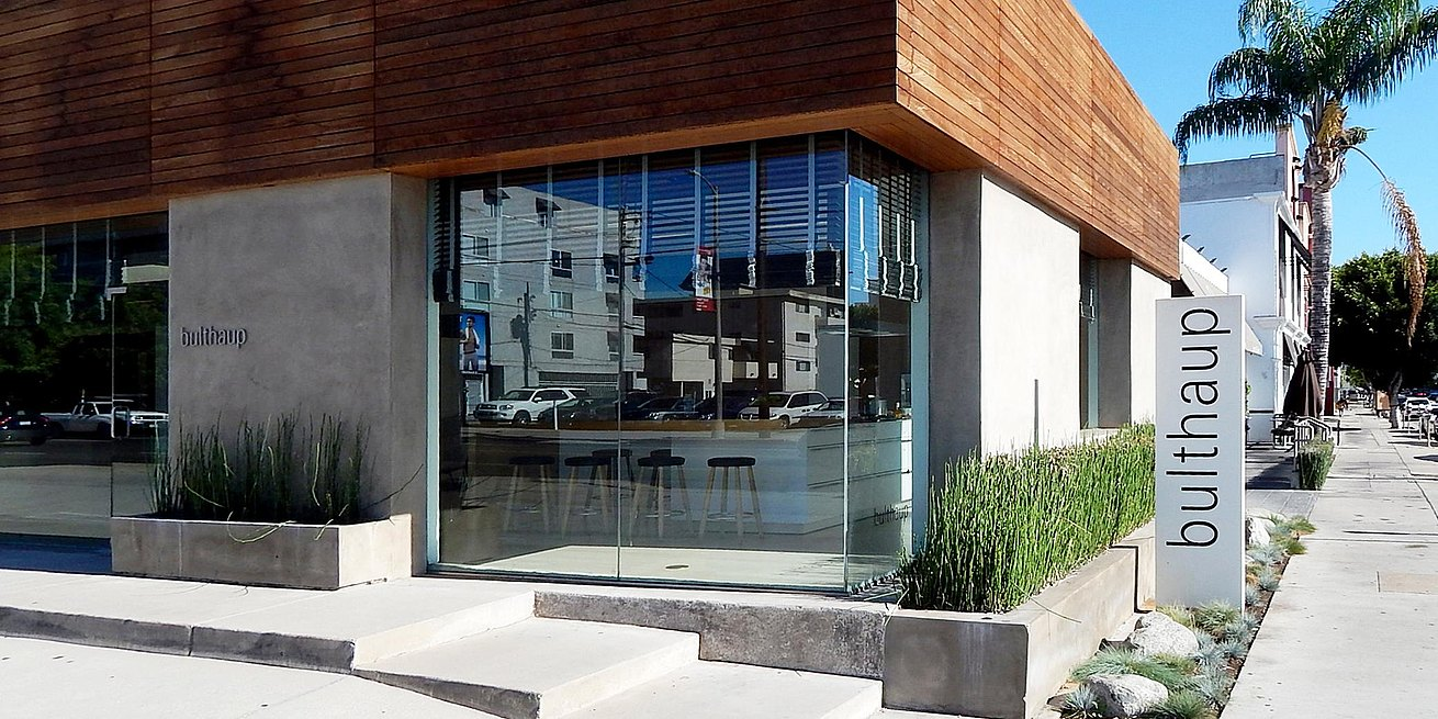 Exterior of buthaup Los Angeles showroom in full sunlight with just the hint of a view of the b3 bar top and stools inside.