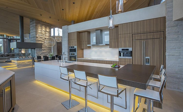 b3 kitchen in vertical walnut and alpine white lacquer showing bar top with longer view into the home glimpsing dining area with pendant lamps.