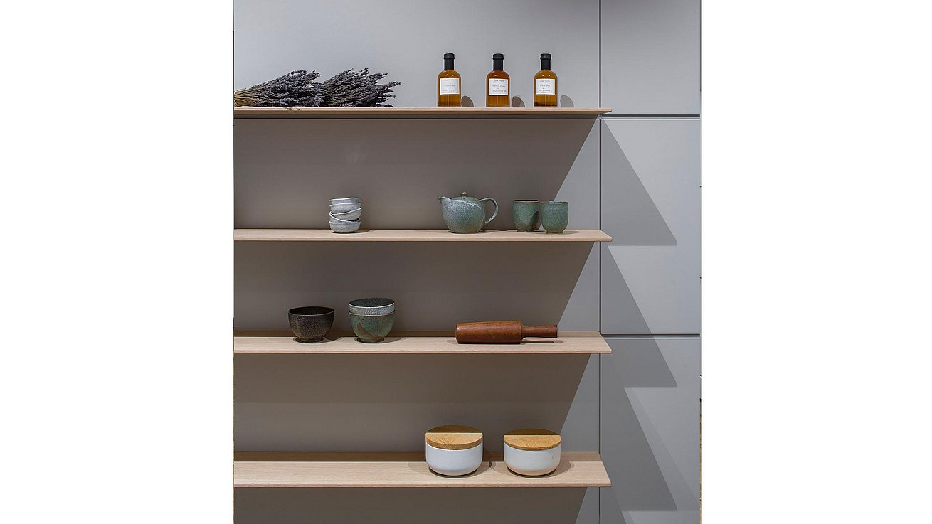 Detail of floating oak shelves presenting special ceramics and bottles of oil.